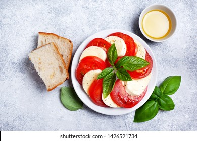 mozzarella and tomato caprese salad with basil on a white plate close-up. view from above