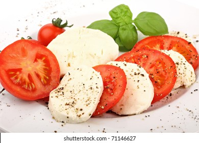 mozzarella and tomato slices with pepper and basilicas.
