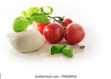 mozzarella, tomatoes and basil herb, Italian caprese, on a light marble plate, corner background fades to white, copy space, selected focus, narrow depth of field