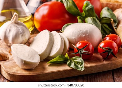 Mozzarella, tomatoes, garlic and basil on wooden board.