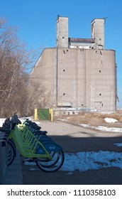 MPLS, MN/USA – APRIL 22, 2018: Docking station of bicycles available for public use and grain elevator in distance at Prospect Park neighborhood of Minneapolis.