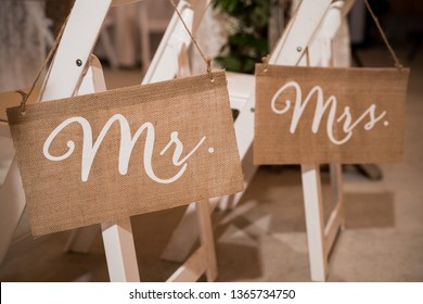 Mr and Mrs burlap signs hanging from white chairs at wedding reception