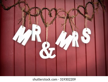 Mr and Mrs White Wedding letters hanging sign with wicker hearts on red wooden background