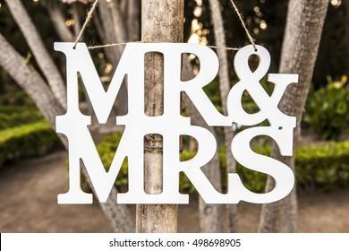 Mr and Mrs White Wedding letters hanging sign from wooden pole with garden on background