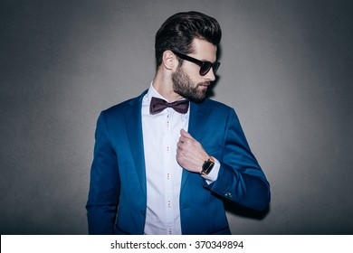 Mr. Perfection. Close-up of handsome young man wearing sunglasses adjusting his jacket and looking over his shoulder while standing against grey background