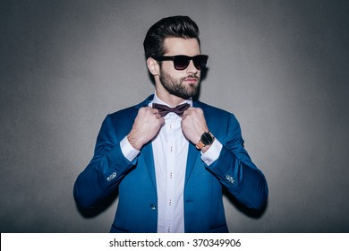 Mr. Perfection. Close-up of handsome young man wearing sunglasses adjusting his bow tie and looking away while standing against grey background