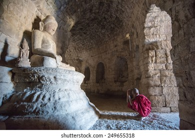 Mrauk U, MYANMAR - DEC 13, 2014: Young  neophyte praying in a Buddihist temple in Mrauk U on December 13, 2014 in Mrauk U, Myanmar.
