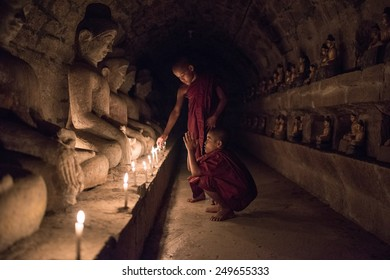 Mrauk U, MYANMAR - DEC 15, 2014: Young  neophyte praying with candle light in a Buddihist temple in Mrauk U on December 15, 2014 in Mrauk U, Myanmar.