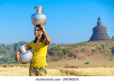 MRAUK U, MYANMAR - JAN 18: Local women carries ewers on Jan 18, 2016 in Mrauk U, Myanmar. Mrauk U is an archaeologically important town in northern Rakhine State, Myanmar.