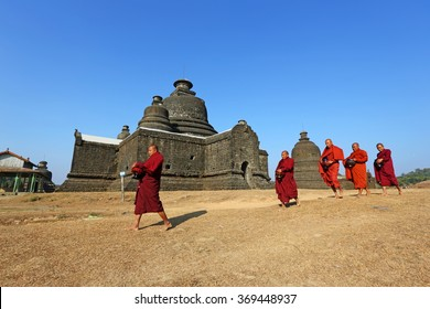 MRAUK U, MYANMAR - JAN 18:Unidentified monks walk to to receive food past Buddihist temple on Jan 18, 2016 in Mrauk U, Myanmar.