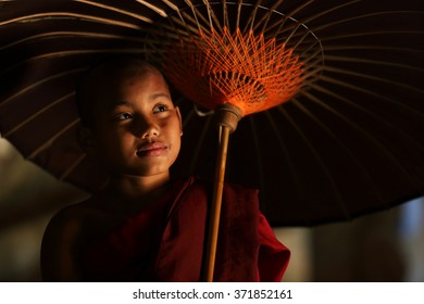 MRAUK U, MYANMAR - JANUARY 18: Unidentified novice monk with red umbrella in buddhist temple on January 18, 2016 in Mrauk U, Myanmar