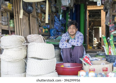 MRAUK U, MYANMAR - JANUARY 30, 2016: An unidentified smiling Burmese shopkeeper poses for a photo at a local market