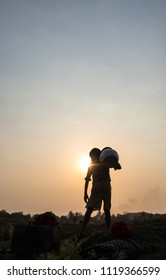 Mrauk u Myanmar on March 20, 2016: a boy was carrying water pot in the sunset time
