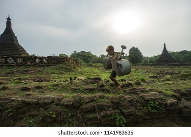 Mrauk u Myanmar on March 29, 2016: Child was carrying water spray jerrycan from farm field