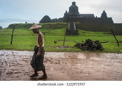 MRAUK U, MYANMAR - SEPTEMBER 1, 2017: A Rakhine man walking past Dukkanthein (or Htukkanthein) Paya, a Buddhist temple built in 1571 with a mushroom-shaped dome in the Arakanese city of Mrauk U