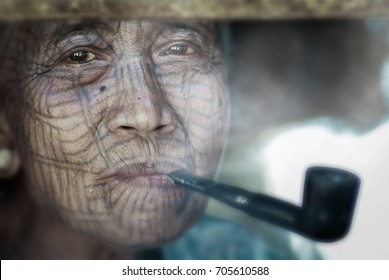MRAUK U, RAKHINE STATE, MYANMAR - MARCH 8, 2012 : Portrait Selective Focus of Elderly Chin Woman Facial Tattoos Smoking Tobacco Pipe, Lemro River Valley.