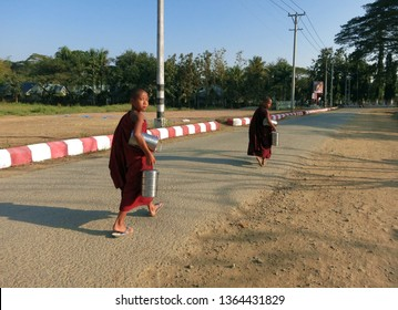 Mrauk-U, Myanmar - February 6, 2016: Two child buddhist monks walking along the road in red garments with Tiffin carriers (dabbas) in hand