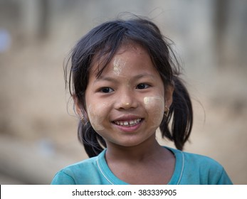 MRAUK-U, MYANMAR - JANUARY 26, 2016: Unidentified young Myanmar girl with thanaka on her smile face is happiness. Thanaka is a yellowish-white cosmetic paste made from ground bark.