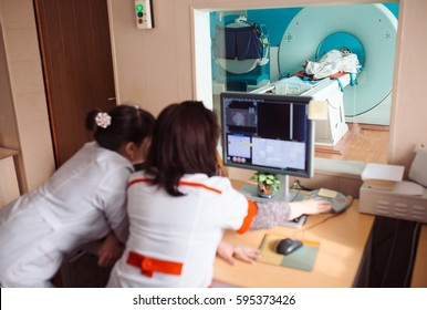 MRI machine and screens with doctor and nurse
