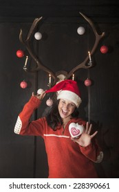 Mrs. Claus standing under decorated antlers, holding heart-shaped Christmas bauble