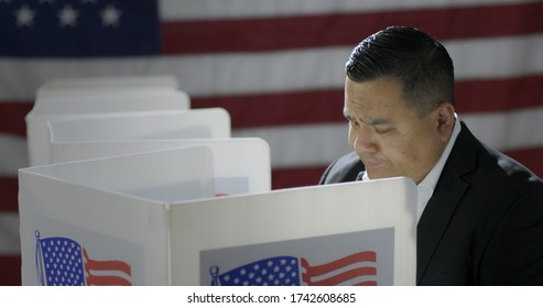 MS Hispanic man in polling station, voting in a booth with US flag in background. Serious expression from high viewpoint