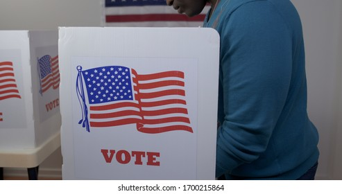 MS side view African American man in blue sweater and face hidden, casting vote in booth at polling station. US flag on wall in background