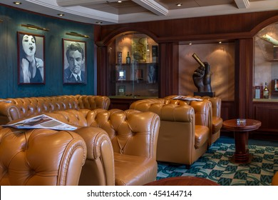 MSC cruise liner - JULY 4, 2016: Luxurious english cigar room with leather armchairs and wooden round table.