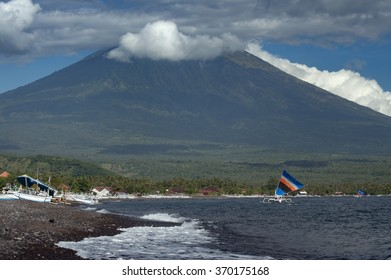 Mt. Agung, Bali, Indonesia. The volcano, Gunung Agung, which last erupted in 1963 looms large over the small fishing village in the Amed area of Bali Indonesia. Fishing boats return in the morning.