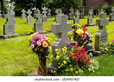 Mt. Angel, Oregon - August 20, 2020: Old Roman Catholic  cemetery with flowers and headstones of former Benedictine monks at a seminary.