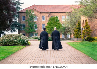 Mt. Angel, Oregon, USA - April 26th, 2020 Two Benedictine monks chatting while walking in the famous historic Mount Angel Abbey