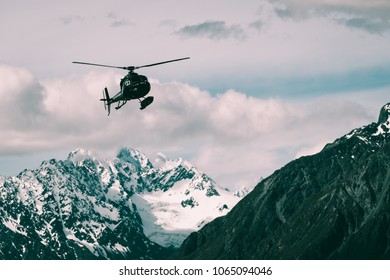 Mt Cook, New Zealand - Dec 4, 2016: Tourist helicopter flys in the mountain area in Mt Cook National Park, New Zealand. The helicopter service offers scenic flights, glacier landing, emergency rescue.