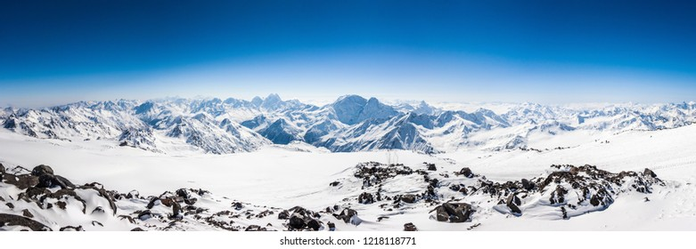 Mt. Elbrus ski slope and the Greater Caucasus ridge with the Mt. Ushba on the horizon at winter sunny day. View from Pastuchova kliffs at Mt. Elbrus, Kabardino-Balkaria, Russia
