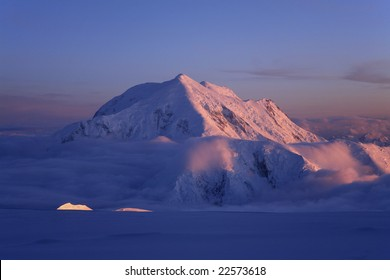 Mt. Foraker above a sea of clouds, lit up by the arctic's midnight sun, as seen from Denali, Denali National Park, Alaska.