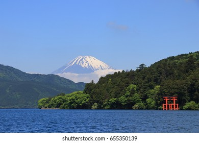 Mt. Fuji and a big red Torii (Gate to the Hakone Shrine) on the Ashinoko Lake under a clear sunny sky. Photoed in Hakone, Japan.
