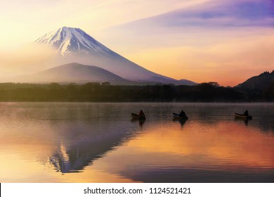 Mt. Fuji or Fujisan with Silhouette three fishermen on boats and mist at Shoji lake during dawn and sunrise in Yamanashi, Japan. Landscape with beautiful skyline reflection on the water.