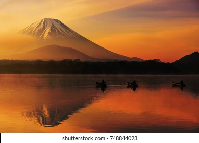 Mt. Fuji or Fujisan with Silhouette three fishing people on boats and mist at Shoji lake with twilight sky at sunrise in Yamanashi, Japan. Landscape with beautiful skyline reflection on the water.
