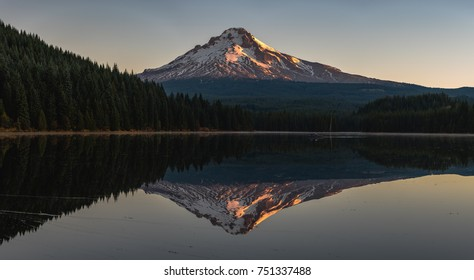 Mt Hood morning on Trillium Lake with a perfect reflection on the water and fishermen in a small boat