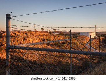 Mt Isa, Queensland, Australia - June 15th 2019: Barbed Wire Fence at the top of the Mt Isa Lookout in Queensland Australia. Landscape views of a Winter sunrise in the large Mining town.