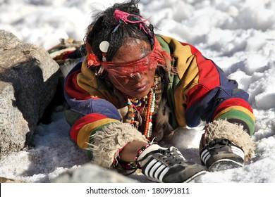Mt Kailash, Tibet, China - May 26, 2012: Buddhist woman pilgrim making the kora (circumambulation) around Mt. Kailash and performing full body prostrations