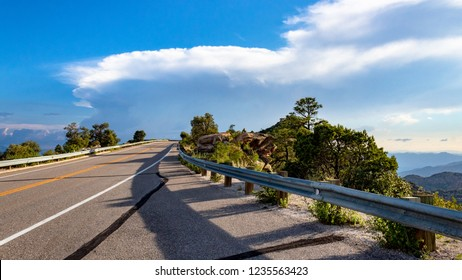 Mt. Lemmon Highway, a scenic mountain roadway with dizzying views of southern Arizona from one of the Sky Islands. Monsoon clouds, against a blue sky, green trees, pavement with a guardrail. 2018.