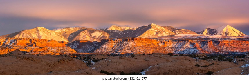 Mt. Mellenthin & Mt. Peale rise above the mesa at sunset, seen from the Sand Flats Recreation Area in Moab, Utah.