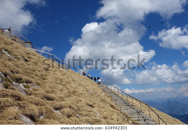MT PILATUS, LUCERN,SWITZERLAND - APRIL 10,2017 - Stairs to the top of Mt Pilatus with some tourists walking up there late afternoon in Spring time