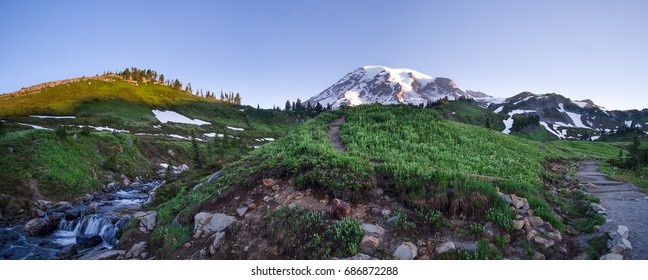 Mt. Rainier panorama at sunrise. Waterfall, paths and wildflowers in the foreground. Location: Mt. Rainier National Park in Washington state.