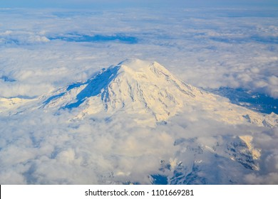 Mt. Ranier from the sky. Experience the grandeur of this Washington area mountain peak from the airplane window. Covered in snow, peaking above a floor of clouds, this inspirational mountain.