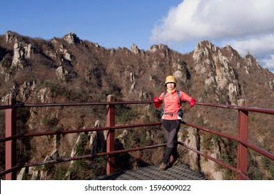 Mt Seoraksan, Yangyang-gun, Gangwon-do, Korea - October 21, 2013: A female hiker is watching at camera on a rocky mountain. Mt Seoraksan is a national park.