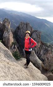 Mt Seoraksan, Yangyang-gun, Gangwon-do, Korea - October 21, 2013:  A female hiker is watching at camera on a rocky mountain. Seoraksan, Mt Seoraksan is a national park.