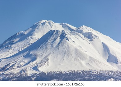Mt Shasta covered in snow in a blue sky background