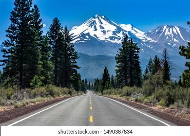 Mt Shasta rises above the landscape beyond rural highway