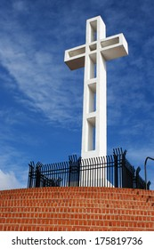 Mt Soledad white cross with blue sky behind it. Red steps lead up to the cross with gate around it.
