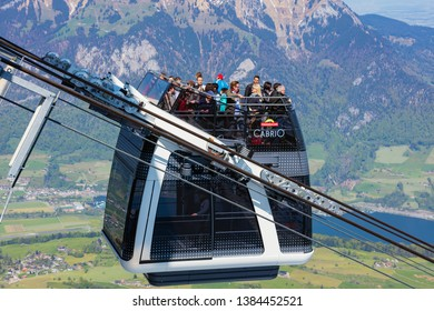Mt. Stanserhorn, Switzerland - May 7, 2016: people in a gondola of the Stanserhorn Cabrio overhead cable car. The Stanserhorn Cabrio is the world's first double deck open top overhead cable car.